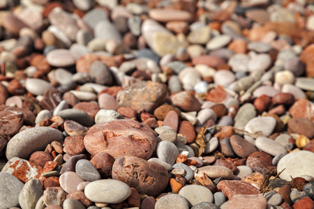 Red pebbles on beach background.  Stock Photo