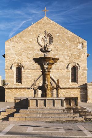 The Grand fountain and Evangelisos church in Rhodes town, Greece. 免版税图像