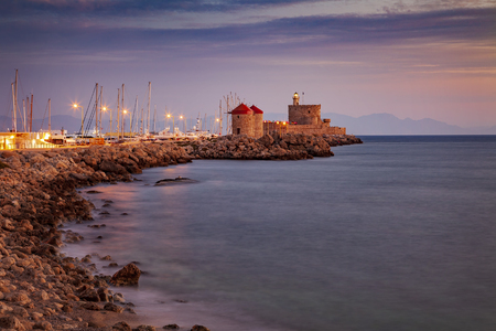 Windmill and fortified lighthouse in Rhodes town marina pier. 版權商用圖片