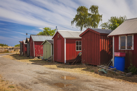 Red fishing huts on the beach in Vik, Sweden.