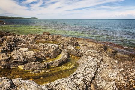 Circular geological feature on rocky beach. Vik, Sweden.