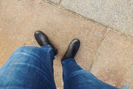 Above view of two legs in denim and boots. Banco de Imagens