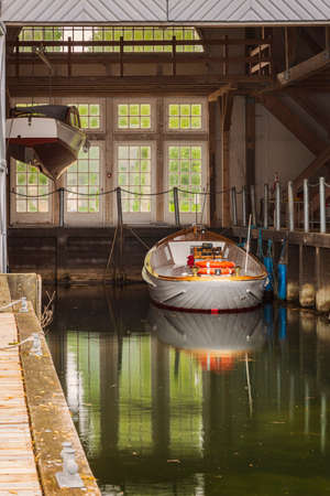 Boat in boat house by lake.