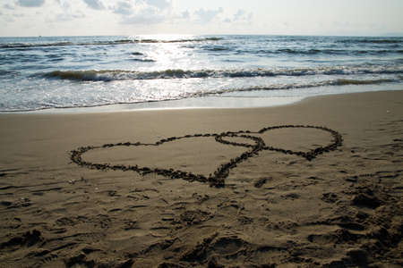anniversary beach: Heart written on the beach to show the love