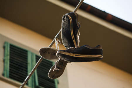 prank: Lots of shoes hanging from a cable Stock Photo