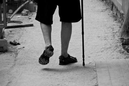 Elderly man walking with the aid of the stick