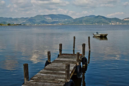 Wooden pier and boat on Lake Massaciuccoli. Lucca Tuscany, Italy  Stock Photo