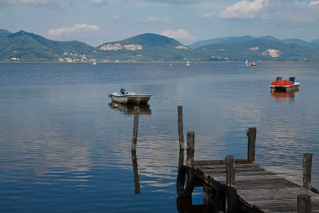 Wooden pier and boats on Lake Massaciuccoli. Lucca Tuscany, Italy  Stock Photo
