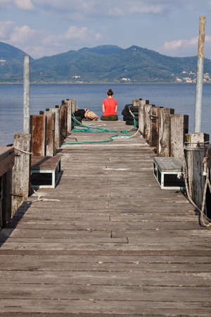 Young girl relaxing on pier  Stock Photo