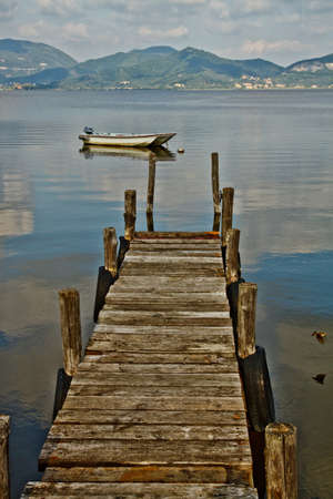 Wooden pier and boat on Lake Massaciuccoli. Lucca Tuscany, Italy  Stock Photo