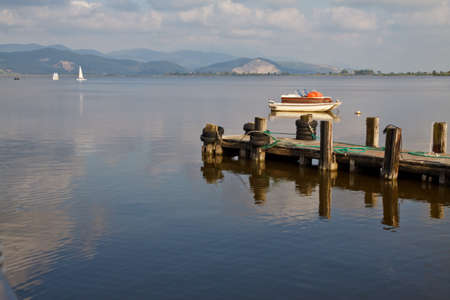 Wooden pier and boats on Lake Massaciuccoli. Lucca Tuscany, Italy  Stock Photo