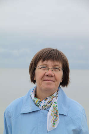 Happy middle-aged woman on the background of the Baltic Sea photo