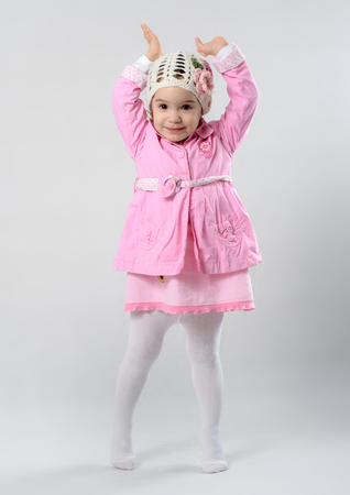 white stockings: Little girl is standing on her tiptoe and raising her hands in the air, she is wearing pink cloths and white stockings