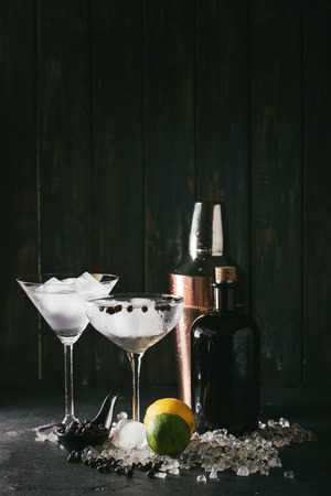Gin and tonic drink served with lime, lemon, juniper berry, copper shaker and ice. Copy space