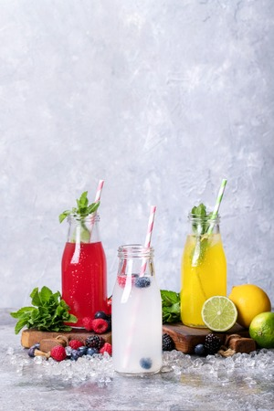 Home made raspberry and lemon lemonades served with different berries, mint, lemons and sparking water, decorated with ice.