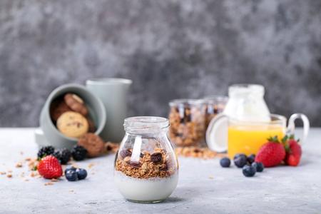 Homemade granola breakfast served with berries, orange juice, yoghurt. Rustic breakfast Concept Imagens - 120950268