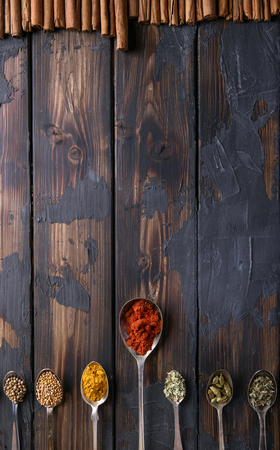 Selection of various spices and herbs in old metal spoons over a rustic wooden background. Top view