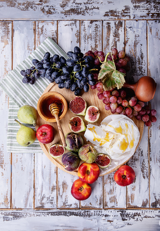 Home made ricotta cheese served with fresh fruit: figs, nectarines, grapes and pears decorated with honey and napkin over a rustic wooden board. Top View