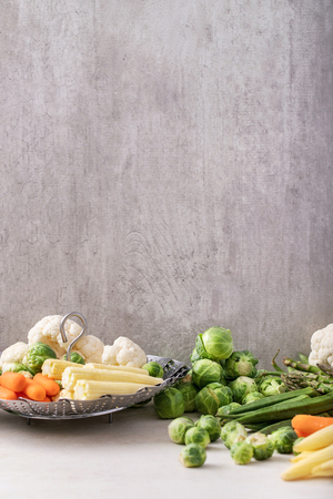 Fresh greens ready to cook: Brussels cabbage, asparagus, baby corn, cauliflower and bamia with metal steamer over a white background. Copy space Stock Photo