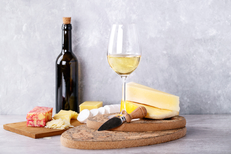Variety of goat and cow milk cheese served with white wine over Portuguese cork boards and grey Background. Copy space