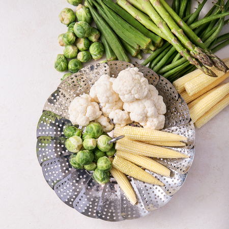 Fresh greens ready to cook: Brussels cabbage, asparagus, baby corn, cauliflower and bamia with metal steamer over a white background. Top view. Square image Stock Photo