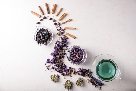 Butterfly pea flower tea served with dry flowers and green tea formed as stars decorated with cinnamon over a light grey background. Herbal drinks concept. Top View Imagens