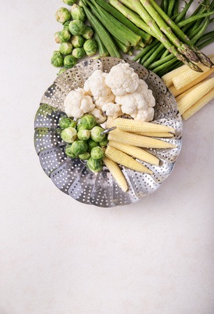 Fresh greens ready to cook: Brussels cabbage, asparagus, baby corn, cauliflower and bamia with metal steamer over a white background. Top view Stock Photo