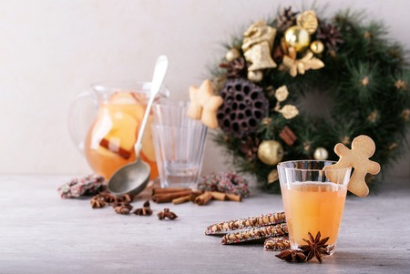 Home made apple punch served with Christmas cookies, spices, decorated with napkin over the grey background