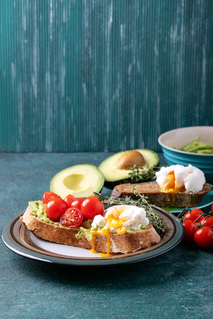 Smashed avocado toast with poached egg served with herbs and tomatoes and guacamole over a green stone background Stock Photo