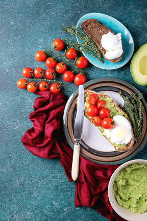 Smashed avocado toast with poached egg served with herbs and tomatoes and guacamole over a green stone background. Top view