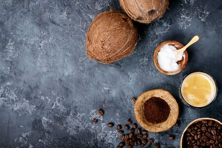 Bulletproof coffee served with ground and whole coffee beans, coconuts, coconut oil over dark texture background. Top view, flat lay. Copy space