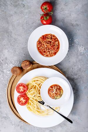 Cooked spaghetti bolognese served with black pepper and saslt in white ceramic plate over white texture background. Top view, flat lay. Copy space Stock Photo