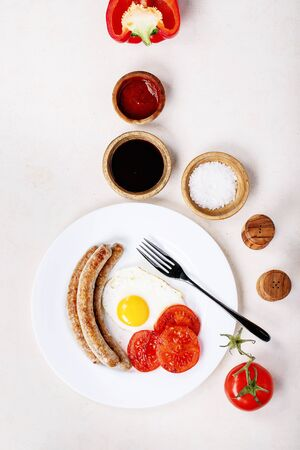 Grilled pork sausages for grill served with fried egg, seasoning, salt, bell pepper, tomatoes and sauces over white texture background. Top view, flat lay. Copy space Stock Photo