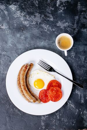 Grilled pork sausages for grill served with fried egg, seasoning, salt, bell pepper, tomatoes and sauces over white texture background. Top view, flat lay. Copy space