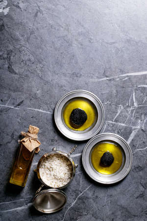 Truffle mushroom on metal plates served with truffle infused olive oil and sea salt with truffles over a black texture background. Top View, flat lay. Copy space