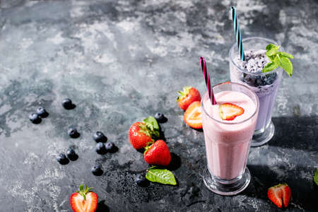 Fresh strawberry and blueberry milkshakes served with berries and mint over dark texture background