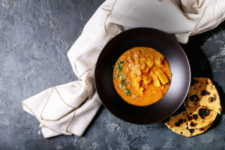 Chicken tikka masala spicy curry meat served in black ceramic plate over wooden background. Top view, flat lay. Copy space