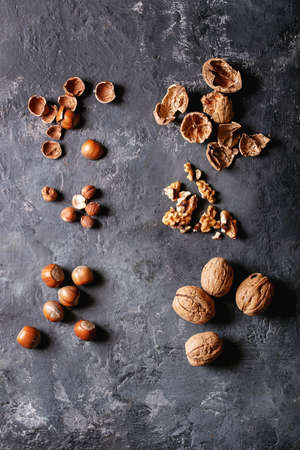 Varieties of nuts: hazelnuts and walnuts over dark texture background. Top view, flat lay. Copy space