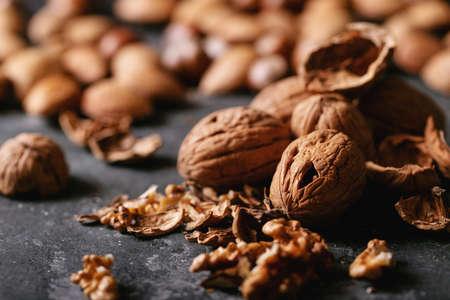 Varieties of nuts: almonds, hazelnuts and walnuts over dark texture background
