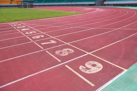 norms: red plastic runway and numbers in a sports ground