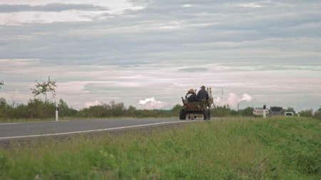 on the new road after repair peasants go on fires and horses, old transport, poor people on transport are overtaken by modern cars, people out of modern civilization Archivio Fotografico