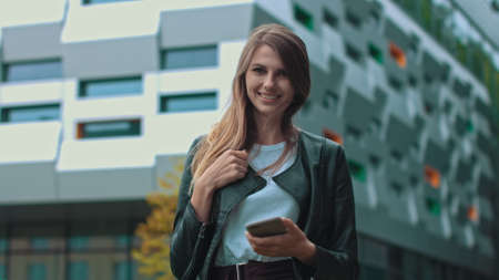 Good looking girl with Long Brown Hair Looking at Her phone Typing and Smiling. Enormous industrial Building at the Background. Green Bushes and Trees. Smart clothes. Natural makeup.