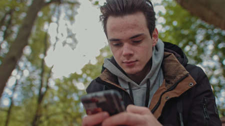 Teenager Looks at the phone, dials a message on a touch screen phone. Shooting close up of a smile on his face. The guy is sitting in the park on a bench. Corresponds with friends 写真素材