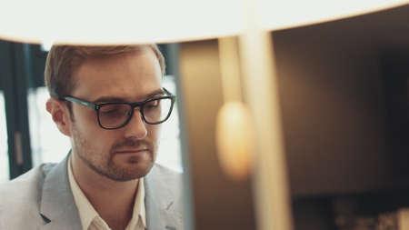 Male eyes in eyeglasses in front of laptop. Coder, programmer or developer using laptop. Close up of glasses