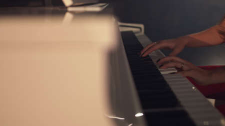 Woman pianist plays gentle classical music on a beautiful grand piano with close-up in slow motion. Piano keys close up in dark colors. Student trains to play the piano