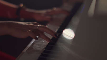 A female young hands playing piano in black manicure and accessories. Classical music pattern. Girl playing piano keywords