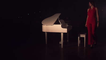 A young beautiful girl in a red dress approaches the white piano and sits down. Connet of classical music. Romantic atmosphere hall filled with smoke