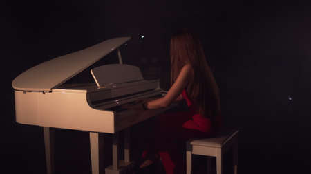 Pianist plays beautiful white grand piano on stage in concert . View from the back.Young beautiful girl in a red dress and plays the piano in a black room with a slight feeling of smoke