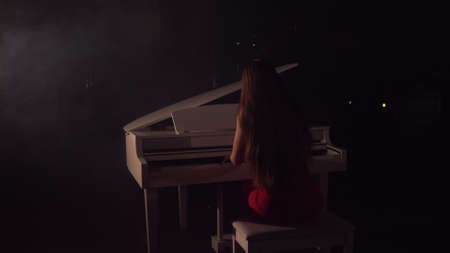 4K Footage Of Female Pianist Plays In Beautiful Grand Piano On Stage In Concert . A woman plays the piano in the concert hall. Stage light and light fog on the background