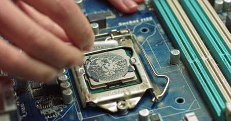 The repairman cleans the CPU of the laptop from the old thermal grease. Electronics and computer concepts service. Repair of computer boards